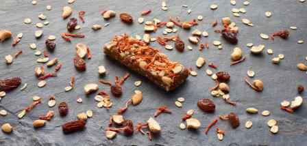 Image 3 - Wild Trail Carrot Cake bar unwrapped (with selected ingredients scattered on slate)